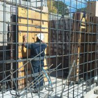 setting up forms around steel rebar structure of walls